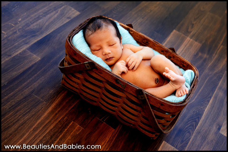 baby sleeping in basket professional newborn baby photography