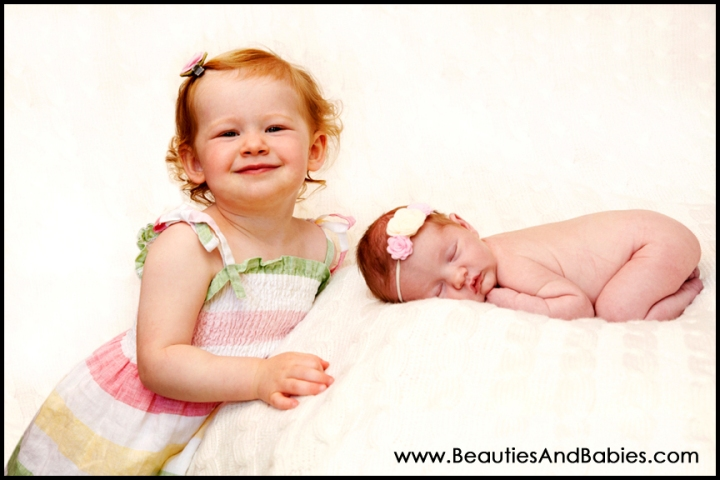 professional pictures of sisters toddler and newborn baby girls