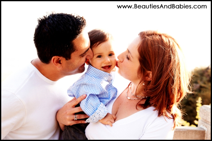 mom and dad kissing baby professional family portrait photography