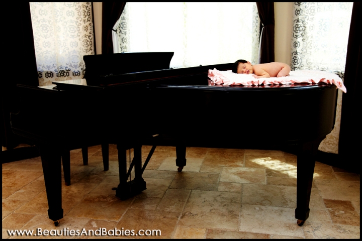 newborn baby sleeping on piano professional photography