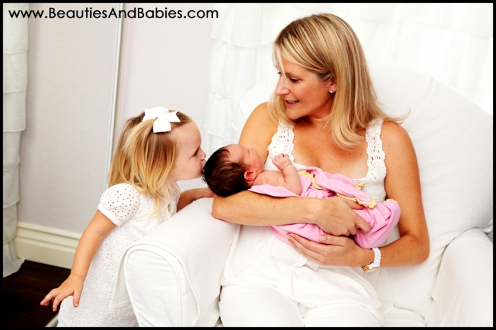 older sibling kissing newborn baby sibling Los Angeles professional photographer