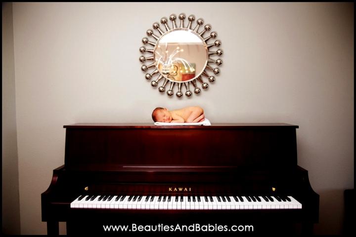 newborn baby sleeping on piano professional photography