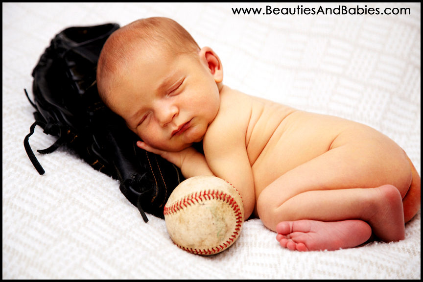 Newborn baby boy sleeping with baseball and glove professional pictures photography