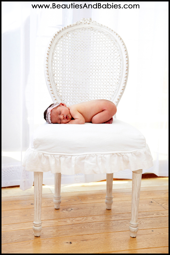 newborn baby sleeping on chair professional photographer