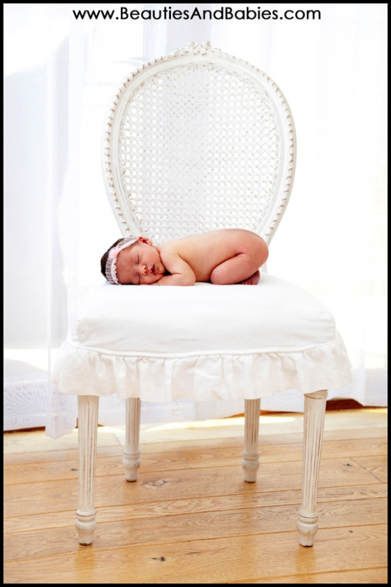 newborn baby sleeping on chair professional photographer