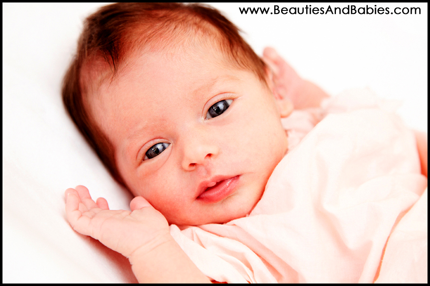 newborn baby girl looking at camera professional photography