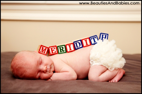 newborn baby girl sleeping with baby blocks professional photography