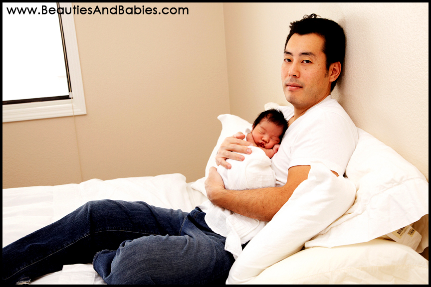 sleeping newborn baby with father professional photography