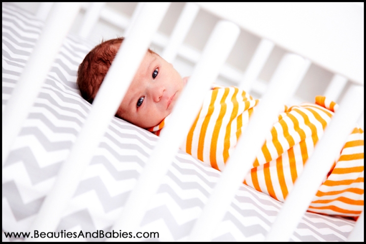 newborn baby laying in crib professional newborn photography