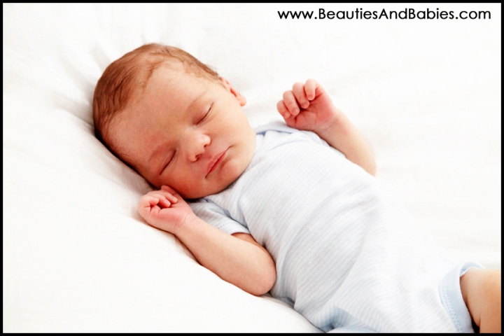newborn baby sleeping on bed professional child photographer