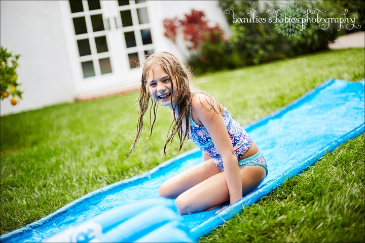 kids lifestyle photography summer fun playing in water with slip n slide professional kids photographer